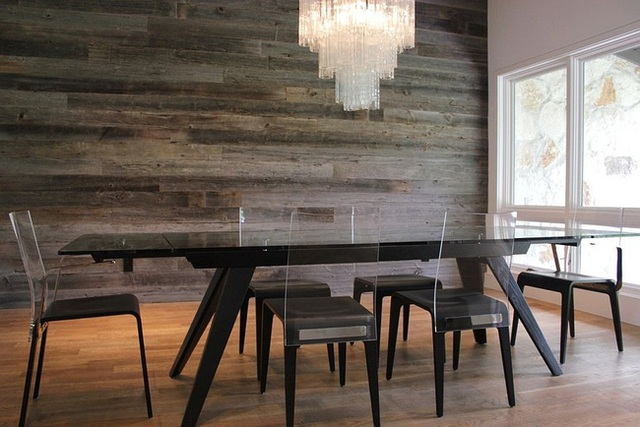 Phòng ăn hiện đại với bàn ăn bằng nhựa acrylic và bức tường gỗ tái chế.