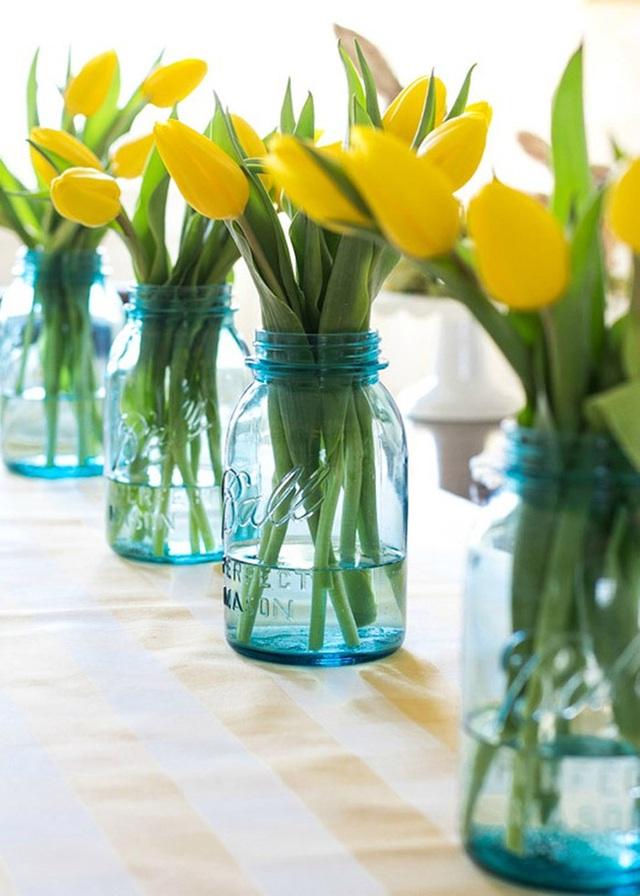 2. Lọ thủy tinh màu xanh dương với những bông hoa màu vàng tươi mới đặt dọc bàn ăn