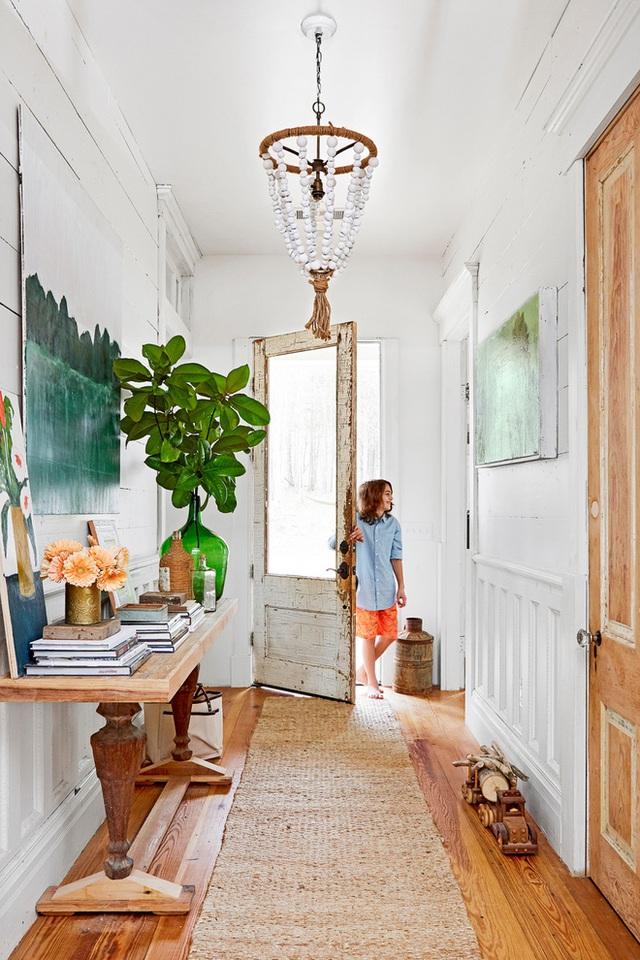 Lối vào nhà đơn giản với thảm bằng chất liệu cói. Màu của sàn gỗ kết hợp ăn ý với nội thất, đồ dùng. Không sử dụng quá nhiều màu nhưng chính sự giản đơn ấy mang đến nét đẹp tinh tế, trang nhã cho không gian vào nhà.