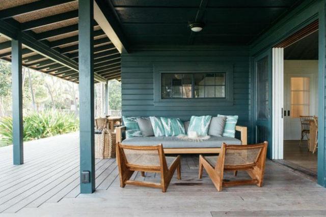 Hiên nhà được mở rộng để tạo khu vực tiếp khách với ghế sofa khung gỗ. Những chiếc gối tựa cũng được chuẩn bị với gam màu nhạt hơn so với màu tường để tạo sự kết nối màu sắc đầy ấn tượng.
