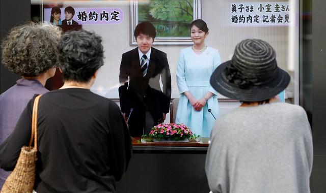 Cặp đôi từng trải qua khoảng thời gian yêu xa khi Công chúa Mako du học. Trong ảnh, người dân Nhật Bản theo dõi thông tin về hôn nhân của công chúa thông qua màn hình ở những địa điểm công cộng. Ảnh: Reuters.