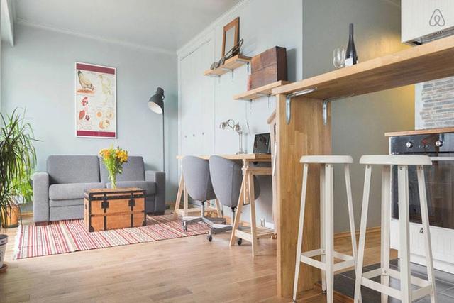 Bên cạnh tủ âm tường là góc làm việc được thiết kế khá ấn tượng với kệ gỗ phía trên, bàn chân gỗ phía dưới cùng ghế xoay êm ái cùng tông màu với sofa.