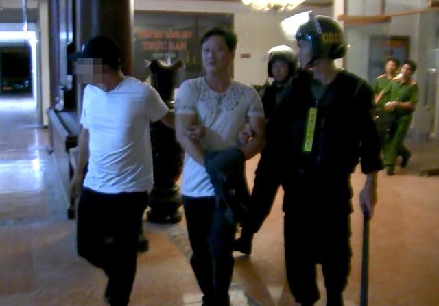 Trịnh Cường cùng các con bạc bị di lí về trụ sở. Ảnh: Thái Linh.