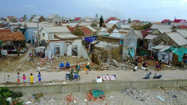 Làng xóm ven biển nhìn từ trên cao, hầu hết những nhà mặt ngoài cùng bị gió bão và sóng biển đánh sập.