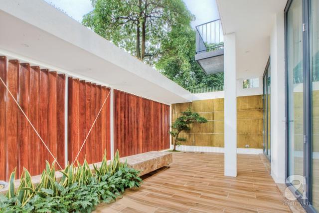 Có thể dễ dàng nhận thấy, trong ngôi biệt thự, chất liệu gỗ được sử dụng ở các phòng, các tầng, tuy vậy cách xử lý màu gỗ ở sắc độ vừa phải, kết hợp cùng những khoảng tường, trần trắng giúp không gian không bị cảm giác nặng nề. Ở tầng 1 là không gian của phòng khách - phòng ăn. Để hưởng trọn vẹn khoảng không gian sân vườn, ở tầng này có cửa kính mở rộng 2 mặt.