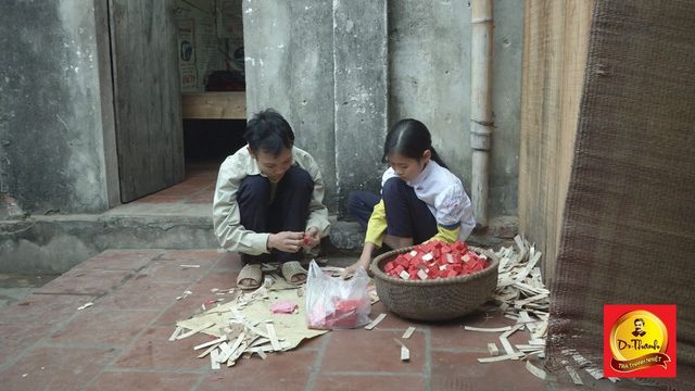 Hai đứa con nhỏ phụ mẹ dán vàng mã để kiếm thêm thu nhập