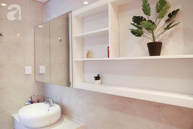Phòng tắm nhỏ với nội thất trắng và tủ gương giúp không gian trông rộng rãi hơn thực tế.
