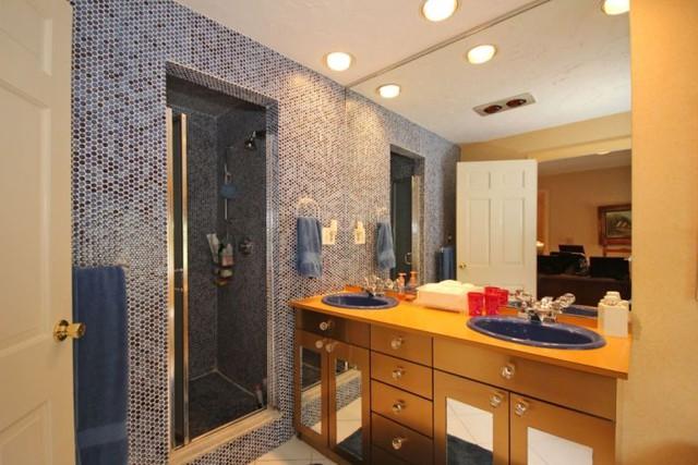 Kệ tủ màu vàng đồng kết hợp cùng mảng tường xanh đậm phía sau khiến căn phòng thêm sang trọng.