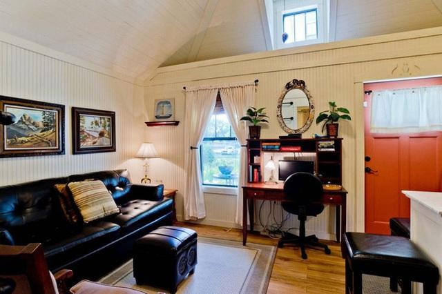 Phòng khách được chủ nhân thiết kế theo phong cách cổ điển với ghế sopha đen tuyền dài, kết hợp với các đồ nội thất tối màu.