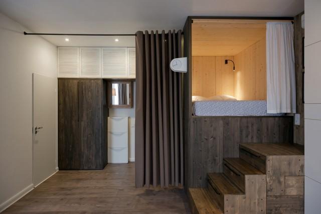Không gian sinh hoạt chính được ngăn cách với khu vực cửa ra vào bằng một rèm lớn cùng màu gỗ.