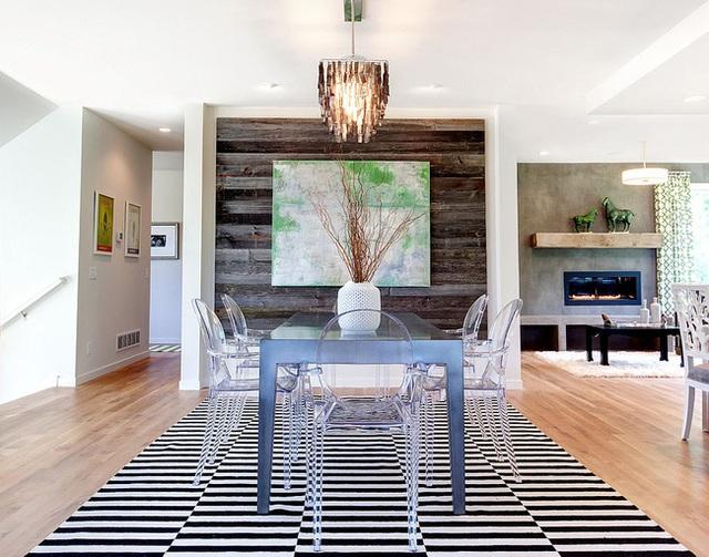 Bức tường gỗ tái chế càng làm nổi bật tone màu của bức tranh treo trên nó, cũng như thiết kế hiện đại của phòng ăn.