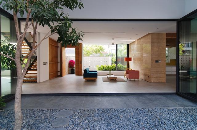 Qua bức tường rào, không gian phòng khách được mở rộng với khoảng sân vườn phía trước và sau nhà, trải dài về phía hồ bơi.