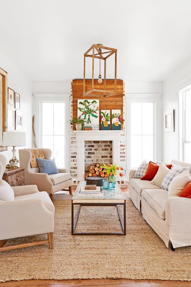 Không gian tiếp khách của gia đình mang đậm chất đồng quê. Toàn bộ căn phòng sử dụng bảng màu trung tính với ghế sofa màu be dịu dàng. Tường phòng được sơn màu trắng, thêm ánh sáng tự nhiên từ những khung cửa sổ giúp cho những màu sắc điểm nhấn của gối tựa thêm bắt mắt.
