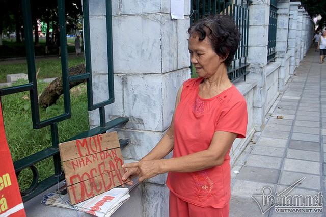 """Tấm biển đơn sơ, dòng chữ viết bằng sơn màu đỏ """"Mời nhân dân đọc báo"""". Thư viện di động của bà đã thu hút cả trăm lượt người tới đọc mỗi ngày"""