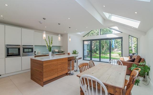 5. Phòng bếp màu trắng theo phong cách tối giản với đảo bếp gỗ ấm cúng và một chiếc bàn ăn bằng gỗ màu sáng.