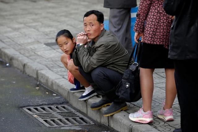 Bé gái và một người đàn ông ngồi xổm chờ xe điện ở Bình Nhưỡng. Hệ thống xe điện và xe buýt hoạt động ở tất cả các thành phố tại Triều Tiên, còn ở vùng nông thôn, chỉ có xe buýt hoạt động.Hệ thống xe điện ở Bình Nhưỡng có từ năm 1962 và vẫn vận hành tới bây giờ.