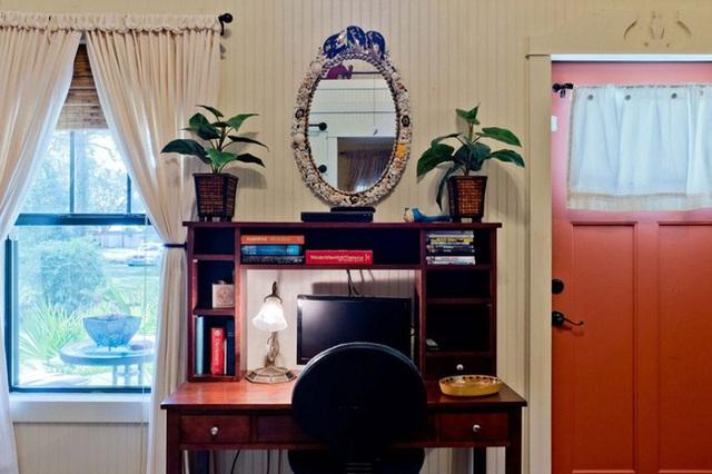 Bàn làm việc được bố trí ngay tại phòng khách, bên trên có cài một gương soi cổ.
