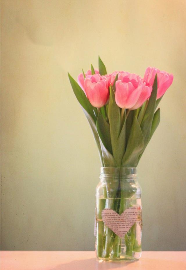 4. Một lọ thủy tinh với miếng giấy báo hình trái tim được dán bên ngoài, cộng thêm những bông tulip rực rỡ sẽ giúp bạn có một góc nhà thật nổi bật.