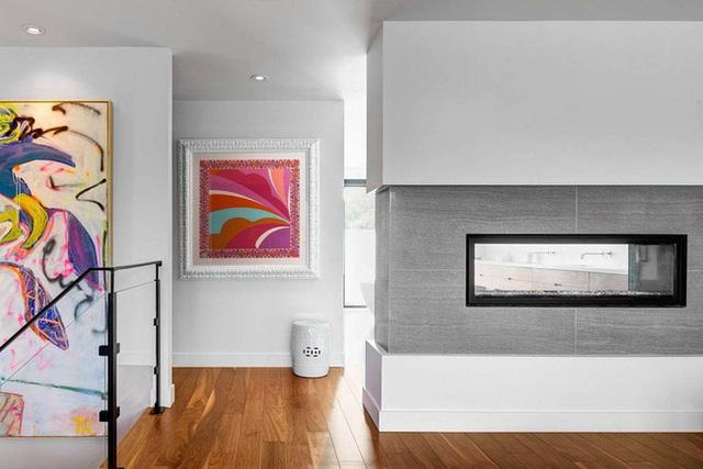 Từ màu sơn tường trắng tinh đến cầu thang được làm bằng thủy tinh trong suốt. Lò sưởi bằng kính cách nhiệt cũng được thiết kế chèn vào giữa bức tường mang lại cái nhìn hiện đại, tân tiến.
