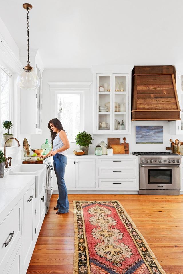 Góc bếp giản dị với hệ thống tủ bếp, tường và trần được chọn lựa gam màu trắng tinh khôi. Kết hợp màu trắng với sàn màu gỗ tạo nét dung dị, bình yên cho không gian chuẩn bị đồ ăn hàng ngày của gia đình.
