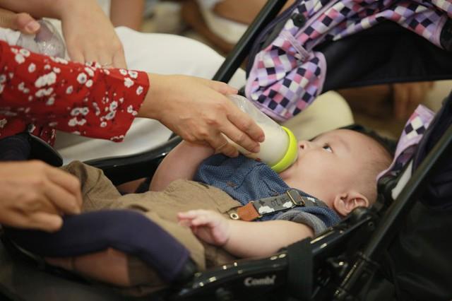 Cậu nhóc được bà cho uống sữa trong lúc chờ chương trình diễn ra.