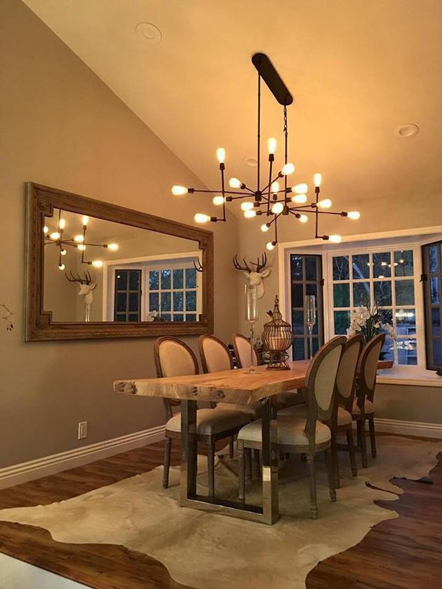 Phòng ăn cổ điển với ghế và bàn gỗ nhưng lại được chấm phá nét hiện đại với chiếc đèn treo.
