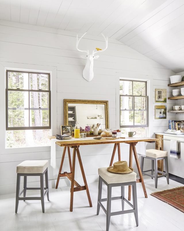 Vì không có đủ không gian để có một bàn ăn sáng và đảo bếp, nên chủ nhà đã tận dụng lại một chiếc bàn làm việc cũ để đáp ứng cả hai nhu cầu sử dụng này. Màu nâu vàng của gỗ tạo cho không gian có cảm giác ấm cúng và gần gũi. Những chiếc ghế đẩu bằng gỗ cũng được sơn màu ghi và bỏ thêm nệm để có thể thoải mái hơn khi ngồi.