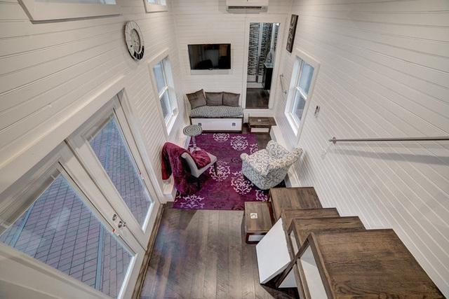 Phòng khách được phân định bằng một tấm thảm hồng tím có họa tiết nổi bật. Đây là cách phân tách không gian khá thông minh cho những căn phòng đa chức năng.
