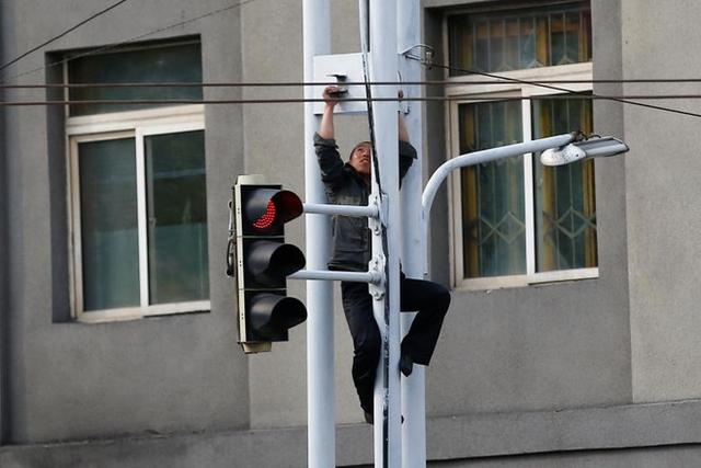 Anh công nhân leo lên sửa chữa cột đèn đường và tín hiệu giao thông.