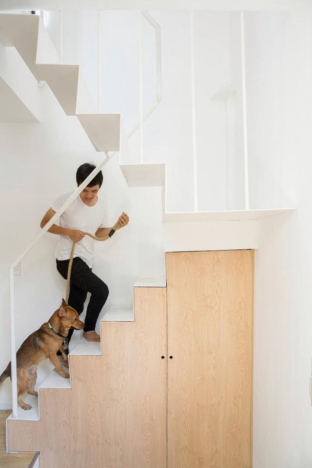 Cầu thang của căn nhà được thiết kế mỏng, đồng màu với tường để tránh gây cảm giác chật chội. Phần gầm cầu thang được sử dụng làm tủ đồ.