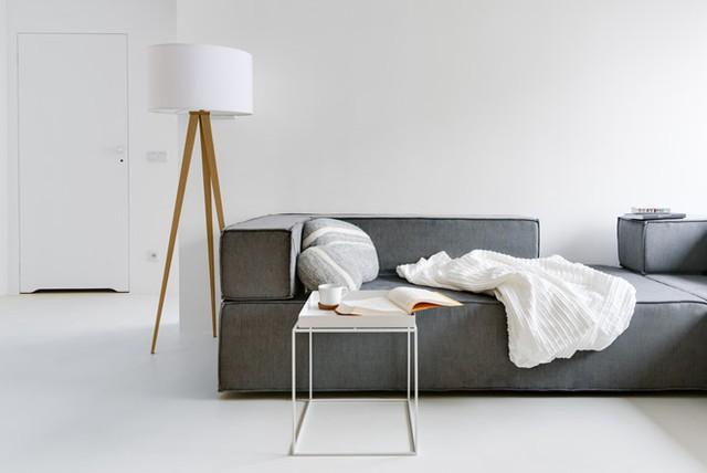 Nội thất thuộc về không gian phòng khách chỉ bao gồm sofa, một chiếc bàn nhỏ thiết kế tối giản giúp thoáng tầm mắt và đèn đọc sách.