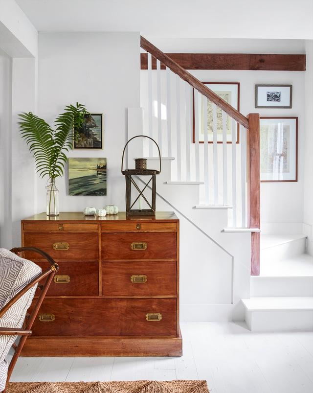 Cầu thang đơn giản màu trắng với tay vịn gỗ.