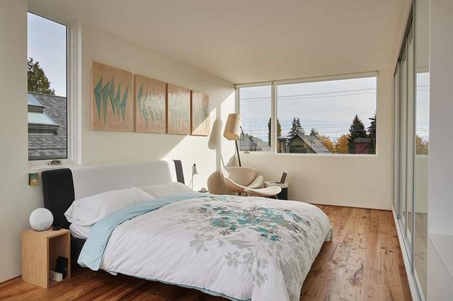 Phòng ngủ thoáng sáng với ô cửa kính rộng mở ngắm trọn khung cảnh thiên nhiên bên ngoài.
