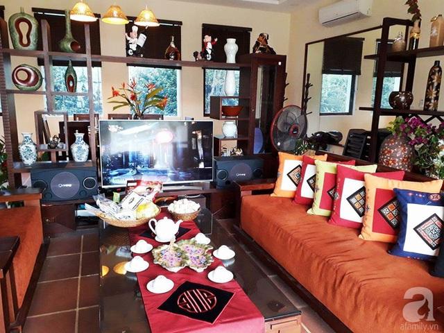 Không gian phòng khách được chọn lựa gam màu trầm, ấm với nội thất chủ yếu bằng gỗ.