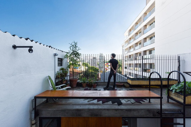 Khu vườn trên sân thượng với ghế băng, cây xanh và một góc view rất thoáng.