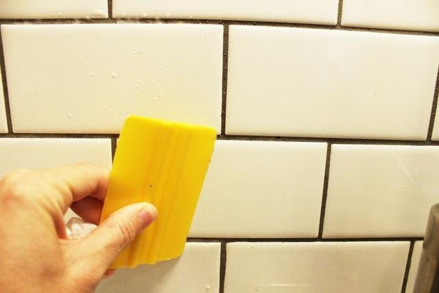 Bạn cần có một dụng cụ cạo bằng plastic có thể bằng nhựa hay chính là một chiếc thẻ tín dụng cũ. Dùng nó để tẩy đi phần vết bám trên tường. Nhớ sử dụng lực nhẹ tránh làm xước men gạch hoa nhé.