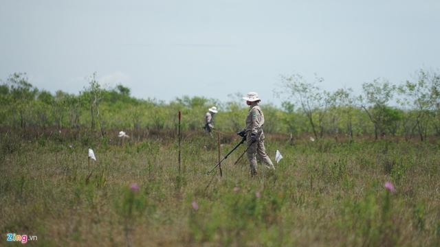 Những nhân viên Renew - NPA dùng máy rà kim loại rà phế liệu chiến tranh trên bãi đất trống. Ảnh: Duy Hiếu.