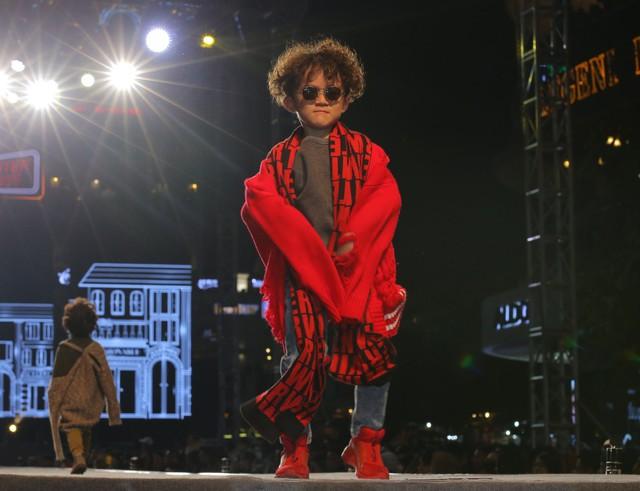 Áo len phá cách, khăn len đỏ phối cùng quần jeans với điểm nhấn cùng tông là đôi sneaker màu đỏ.