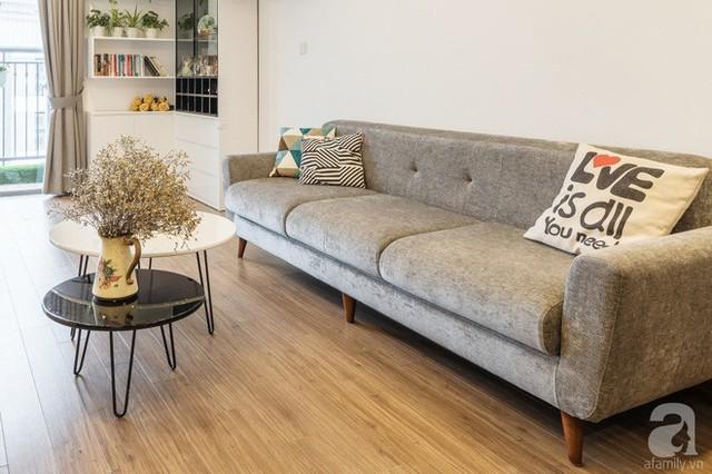Ghế sofa với những đường nét mềm mại kết hợp hài hòa với bàn trà, nơi được trang trí với chậu hoa dịu dàng cho cuộc sống trên cao của gia đình trẻ thêm bình yên.