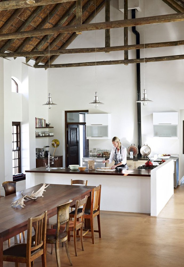 8. Phòng bếp theo phong cách trang trại hiện đại với một lò sưởi và không gian phòng ăn mộc mạc với những chiếc ghế khác nhau.