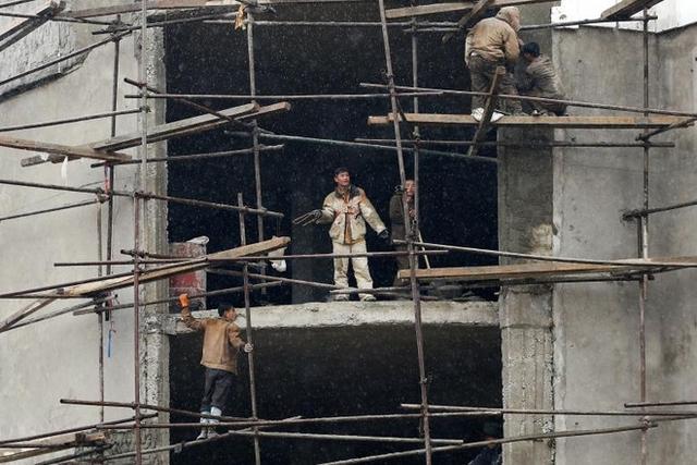 Vài anh thợ xây đang quan sát đồng nghiệp thi công ở một tòa cao ốc.