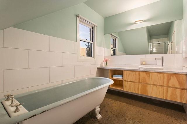 Phòng tắm hiện đại với tông màu xanh patel. Các đồ dùng sinh hoạt được làm bằng gỗ với kết cấu đơn giản.