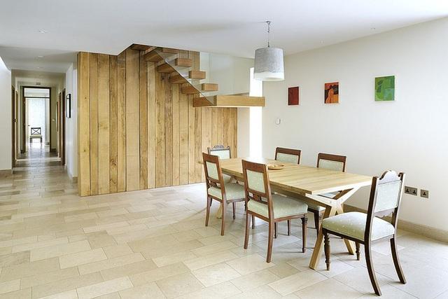 Tường và cầu thang gỗ tái chế tinh tế trở thành phông nền lý tưởng trong phòng ăn này.