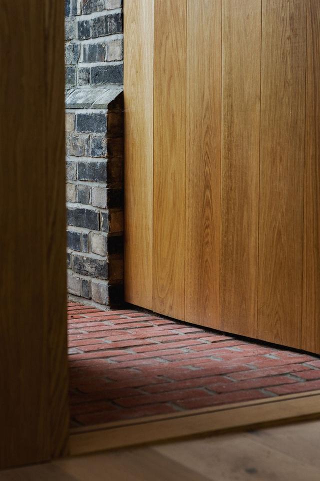Lát gạch nung đỏ cũ đi kèm với cửa bằng gỗ sồi hiện đại, ấm áp tạo cảm giác gần gũi hơn.