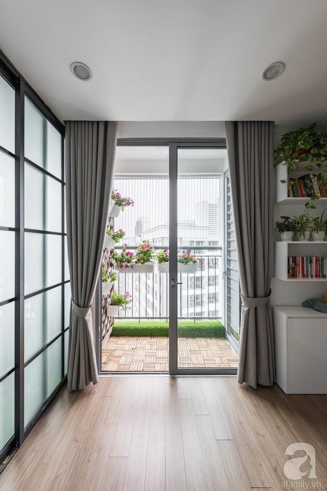 Màu sắc cơ bản được cân bằng trong không gian nhờ sàn gỗ tự nhiên ấm cúng và thân thiện. Phòng khách trở nên đẹp hơn và thoáng hơn nhờ ban công nhỏ xinh được bố trí đơn giản với thảm cỏ nhân tạo gắn ở lan can và phần tường đứng được gắn giá treo những chậu hoa rực rỡ.