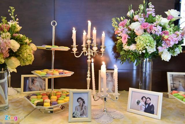Không gian tiệc cưới trang trí sang trọng với hoa tươi, nến, bánh ngọt và ảnh của cô dâu - chú rể.
