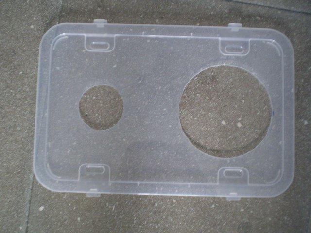 Hai hình tròn trên nắp thùng để gắn quạt (bên phải) và ống chữ L (bên trái)