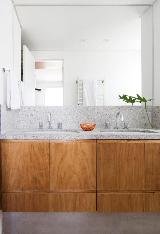 Phòng tắm có một tủ gỗ lớn và kệ bồn tắm làm bằng đá.