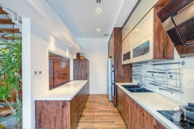 Bếp gọn gàng, hiện đại đặt gần khu vực ăn uống. Đặc biệt bếp có khoảng nhìn ra thông tầng giữa nhà.