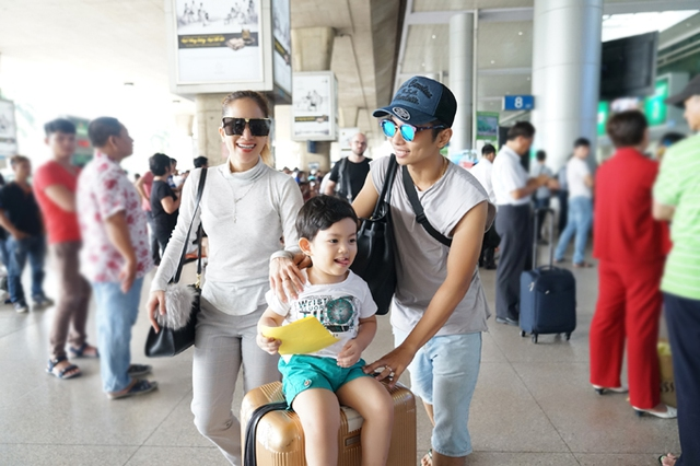 Phan Hiển để Kubi ngồi lên hành lý của vợ và đẩy ra xe.
